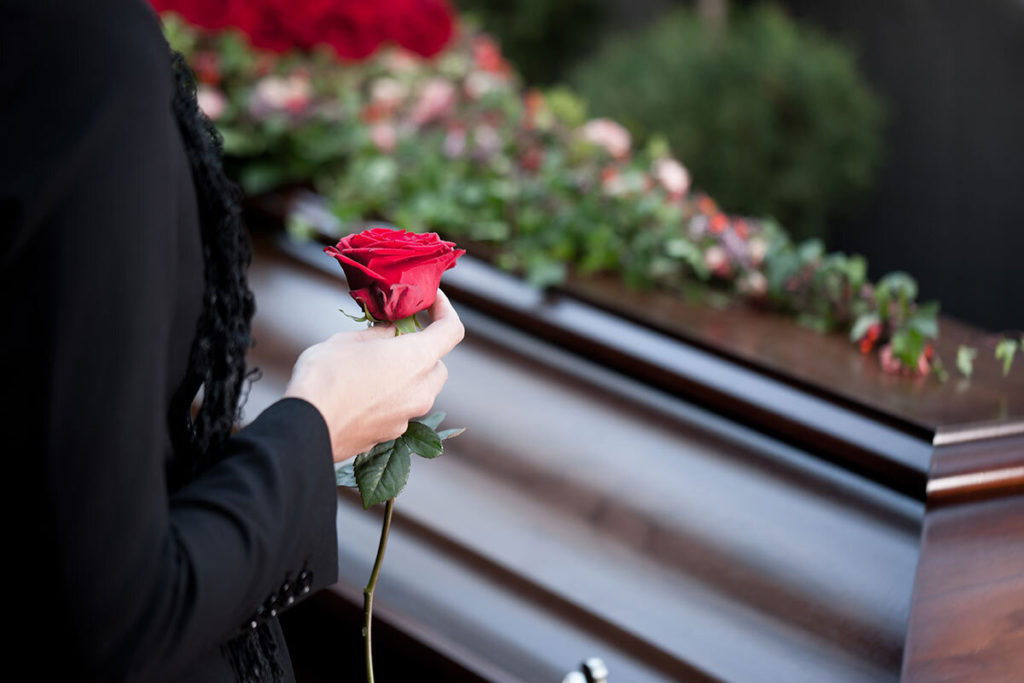 Casket and person holding a rose