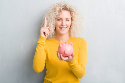 Woman with questions and ideas holding piggy bank
