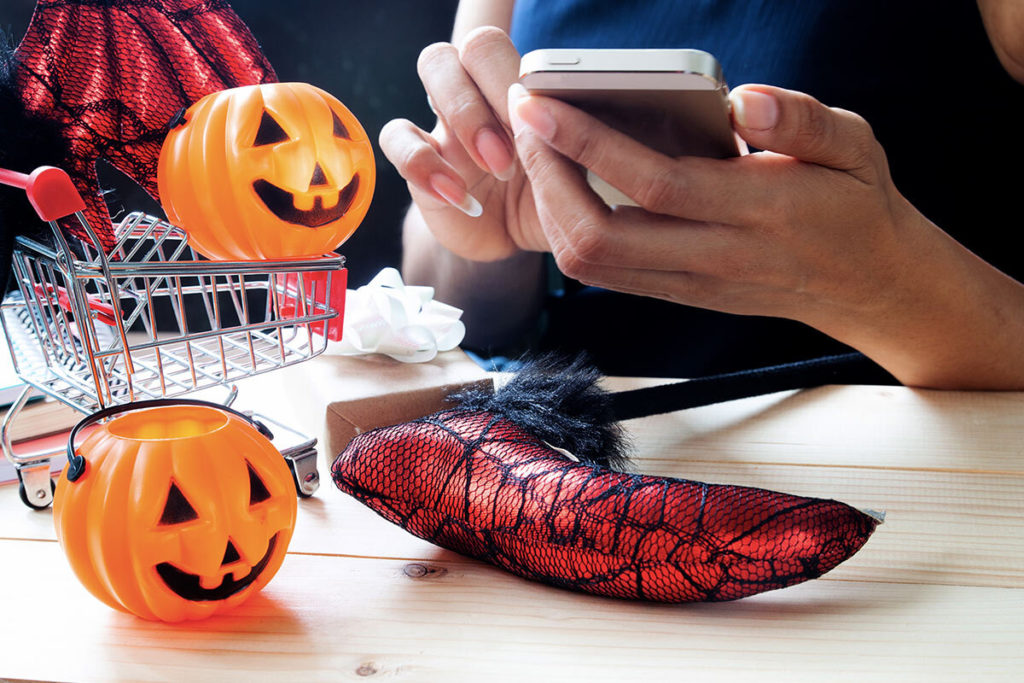 Woman holding her phone shopping for Halloween